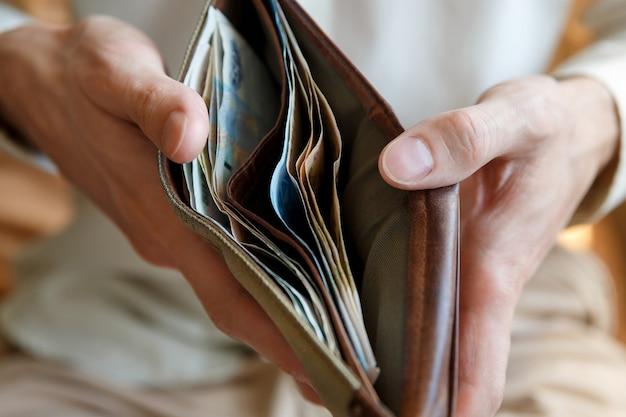 Mains d'homme tenant un portefeuille avec de l'argent dedans