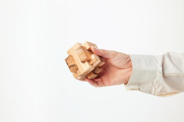Les mains de l'homme tenant un puzzle en bois.