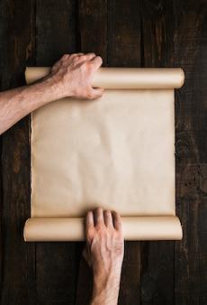 Mains d'homme tenant un rouleau de papier stressé sur le vieux fond de bois de bar. concept créatif de l'expédition wanderlust. espace vide, place pour le texte, le lettrage. maquette de bannière horizontale.