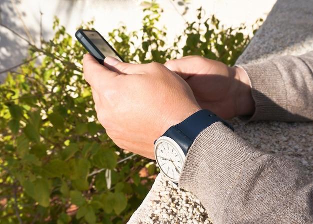 Mains d'homme tenant un smartphone et portant une montre à lanières de caoutchouc