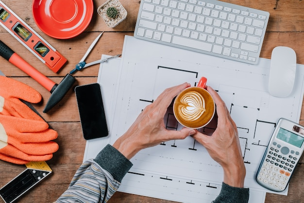 Mains d'homme tenant des tasses de café sur une table en bois rustique