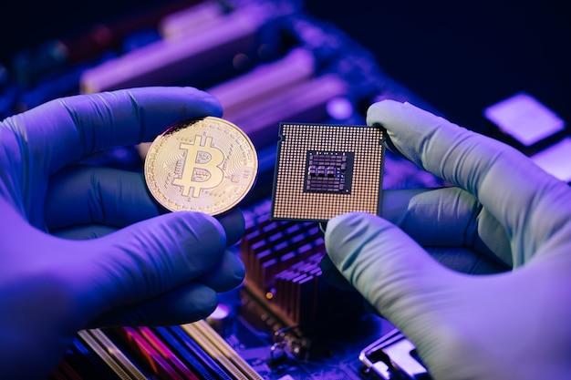 Les mains de l'homme tiennent bitcoin or et cpu sur la carte mère