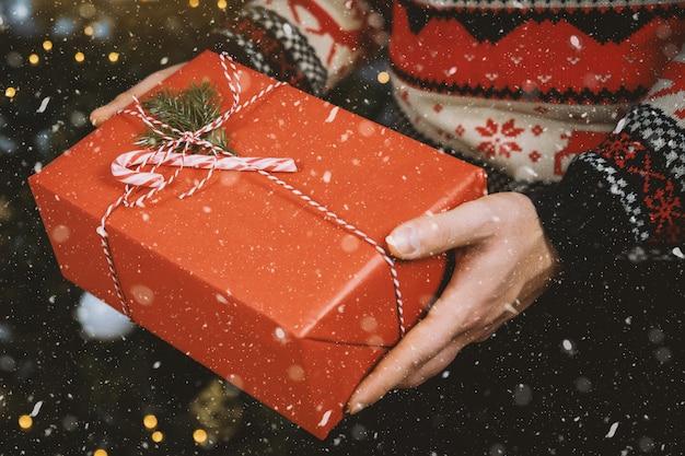 Les mains de l'homme tiennent la boîte de cadeau de noël. joyeux noël