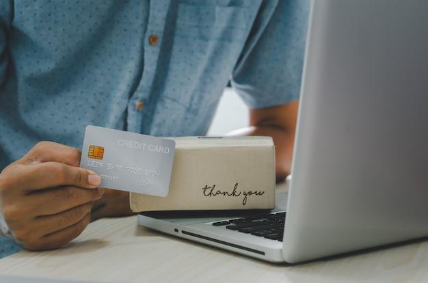 Les mains de l'homme tiennent une carte de crédit et une boîte de colis hématite et ordinateur portable à la table concept d'entreprise de service de livraison en ligne.