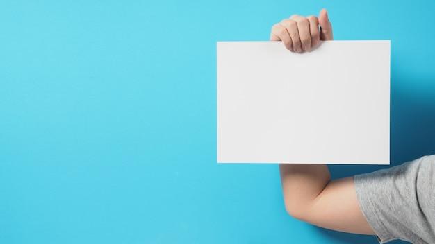 Les mains de l'homme tiennent du papier a4 vide vierge sur fond bleu.