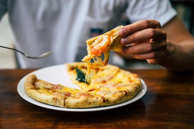Les mains de l'homme tiennent la pizza