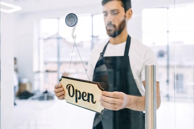 Mains d'homme tournant un signe sur une porte de magasin en verre de fermé à ouvert.