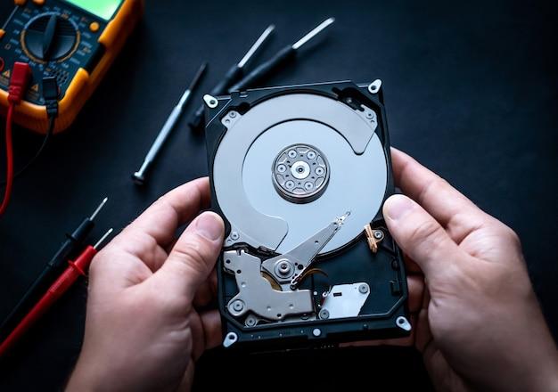 Mains d'homme avec des tournevis et un mutimètre numérique fixant le disque dur