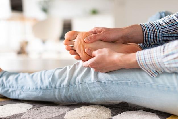 Mains d'homme vous donnant un massage des pieds pour soulager la douleur après une longue marche, en raison de chaussures inconfortables, souffrant de pieds plats