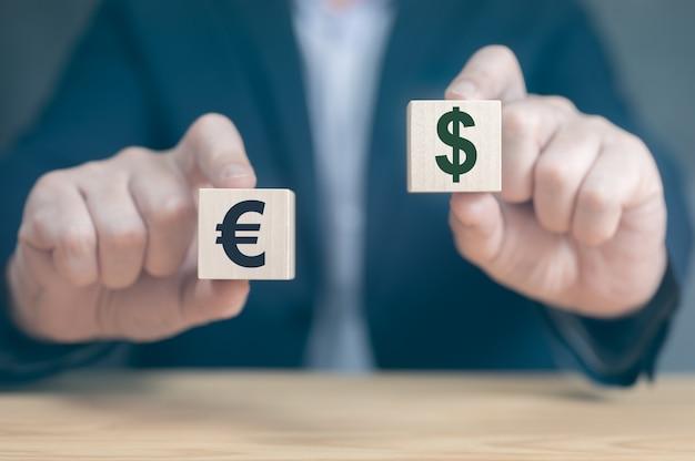 Les mains d'hommes d'affaires de concept de devise tiennent deux cubes en bois avec le signe du dollar et de l'euro