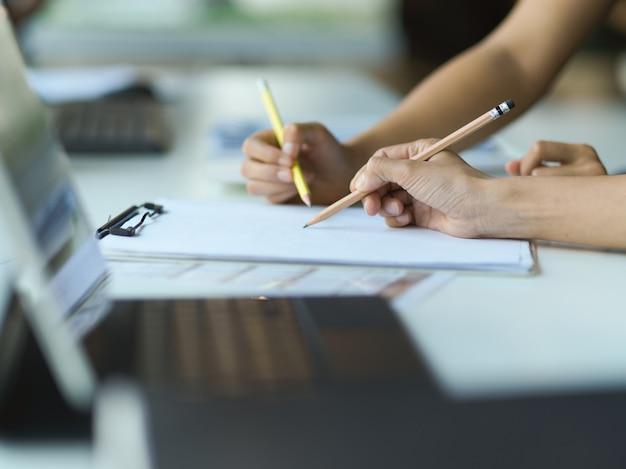 Les mains des hommes d & # 39; affaires avec des crayons en notant sur du papier blanc sur la table