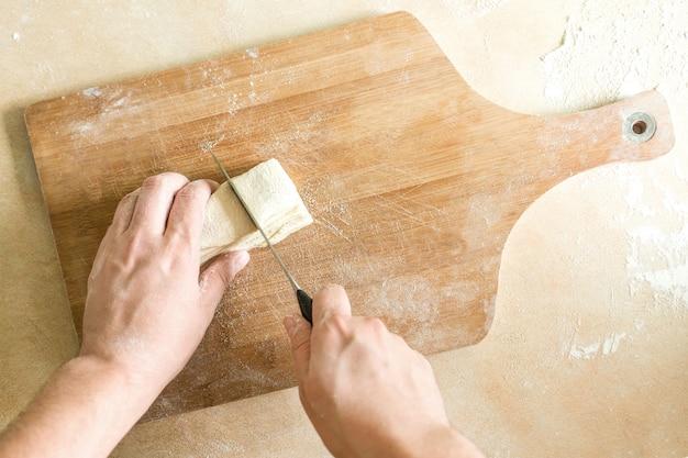 Mains d'hommes coupant la pâte crue