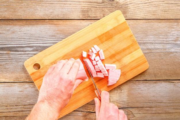 Les mains des hommes coupent la saucisse bolognaise sur une planche à découper