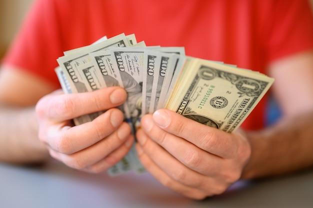 Les mains des hommes détiennent et comptent des billets de 100, 50 et 1 dollar sur une table grise