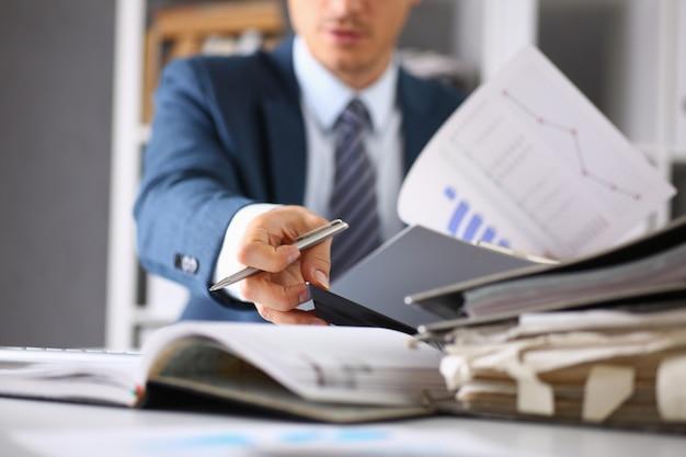 Les mains des hommes détiennent des documents avec des statistiques financières