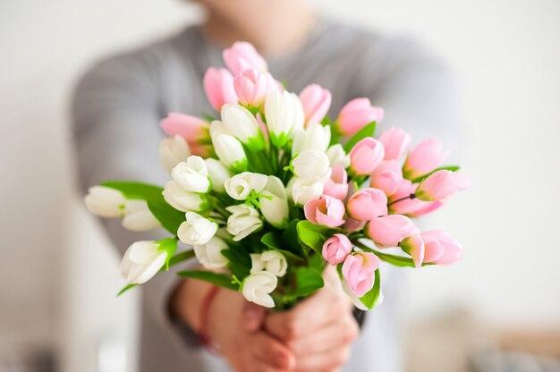 Les mains des hommes étirent un bouquet de fleurs de printemps