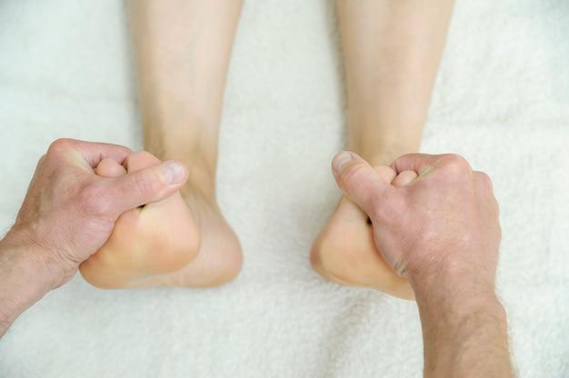 Les mains des hommes massent les pieds.