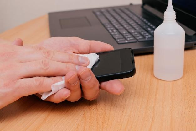 Les mains des hommes nettoient le téléphone avec une lingette humide antiseptique. prévention du coronavirus après avoir visité des lieux publics