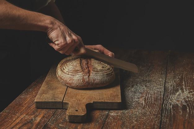 Les mains des hommes ont coupé le pain de seigle rond sur une planche à découper brune en bois