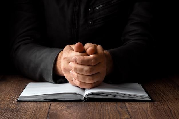 Les mains des hommes en prière sur un fond noir