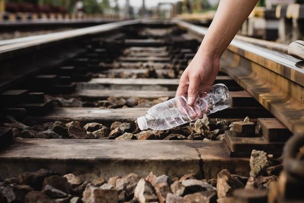 Les mains des hommes ramassent des déchets plastiques sur la voie ferrée