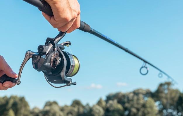 Mains d'hommes tenant une canne à pêche ou un pêcheur sur un ciel bleu clair