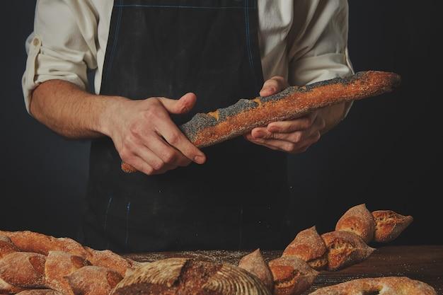 Les mains des hommes tiennent une baguette aux graines de pavot et une table avec différents pains