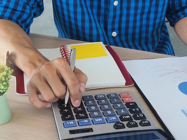 Mains humaines à l'aide d'une calculatrice