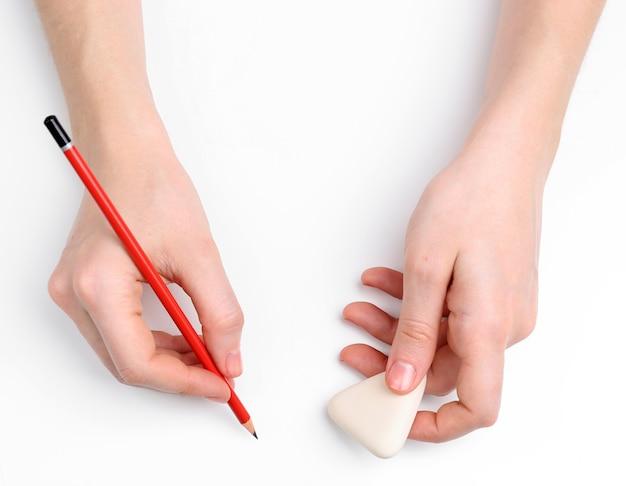 Mains humaines avec un crayon et effacer le caoutchouc, isolé sur blanc