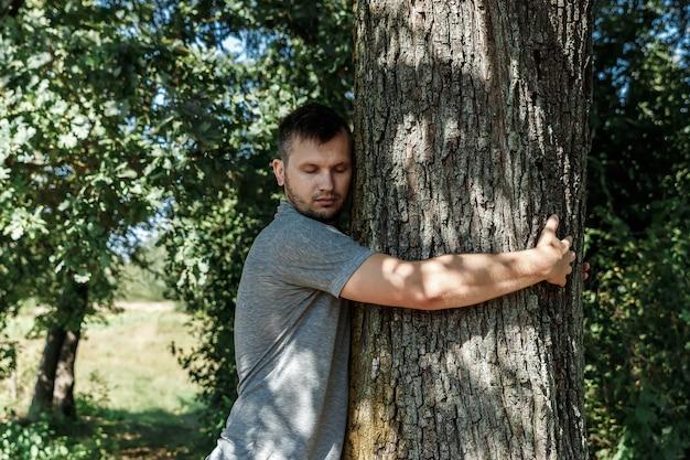 Des mains humaines étreignent, enveloppent un arbre.