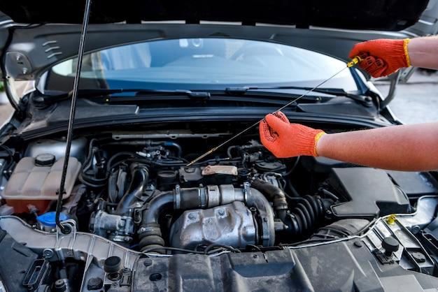Mains humaines avec indicateur de niveau d'huile contre le moteur de la voiture
