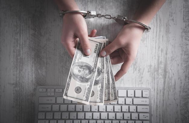 Des mains humaines menottes aux poignets avec de l'argent et un clavier d'ordinateur