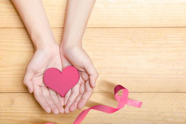 Mains humaines montrant un coeur rose avec un ruban rose sur un fond en bois