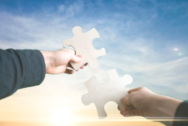 Les mains humaines relient deux pièces de puzzle ensemble, fabrication de desicion, fond de ciel