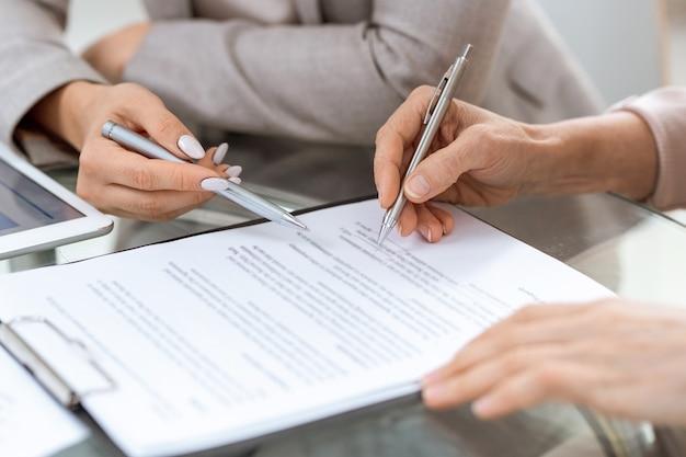 Des mains humaines avec des stylos sur le document financier au moment de la signature après avoir discuté de ses points