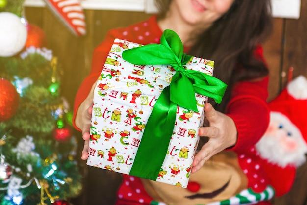 Mains humaines tenant un cadeau. fille tend un cadeau de noël dans une boîte