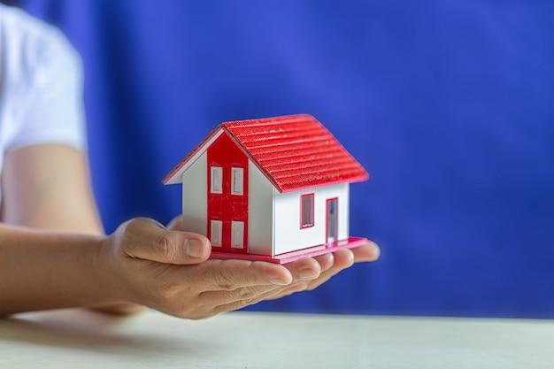 Mains humaines tenant le modèle de maison de rêve