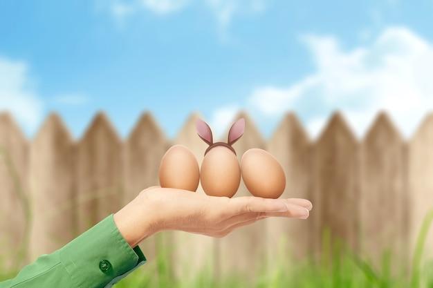 Des mains humaines tenant des oeufs de pâques avec des oreilles de lapin et une clôture en bois. joyeuses pâques