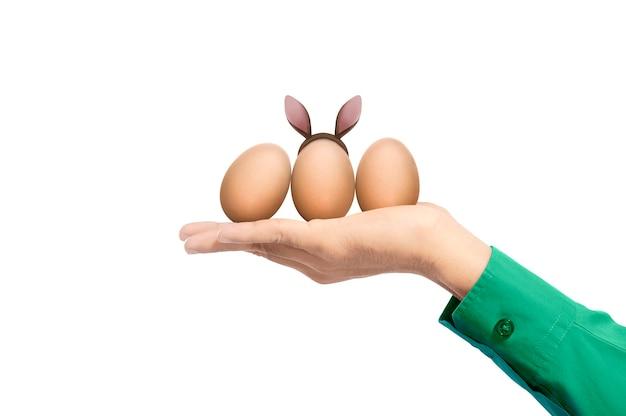 Mains humaines tenant des oeufs de pâques avec des oreilles de lapin isolés. joyeuses pâques