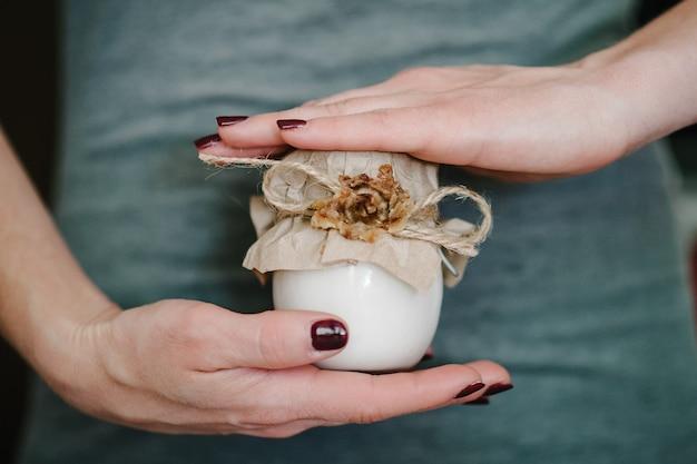 Les mains impeccables de la jeune femme tiennent le pot cosmétique de crème pour la peau sur place isolée.