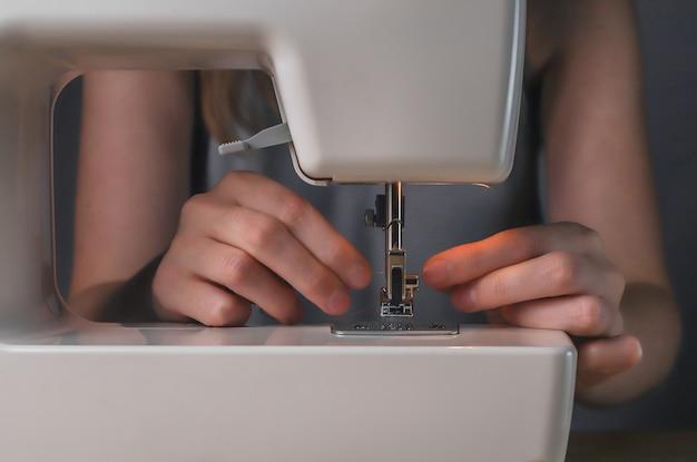 Mains insérant le fil dans le trou de l'aiguille dans la machine à coudre