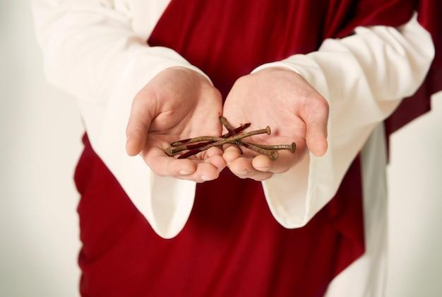 Mains de jésus tenant des clous rouillés