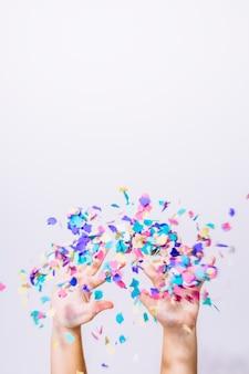 Mains jetant des confettis