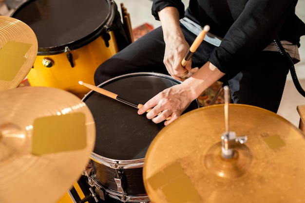 Mains de jeune batteur occasionnel prenant des baguettes du haut du tambour noir alors qu'il était assis par batterie et va commencer la répétition individuelle