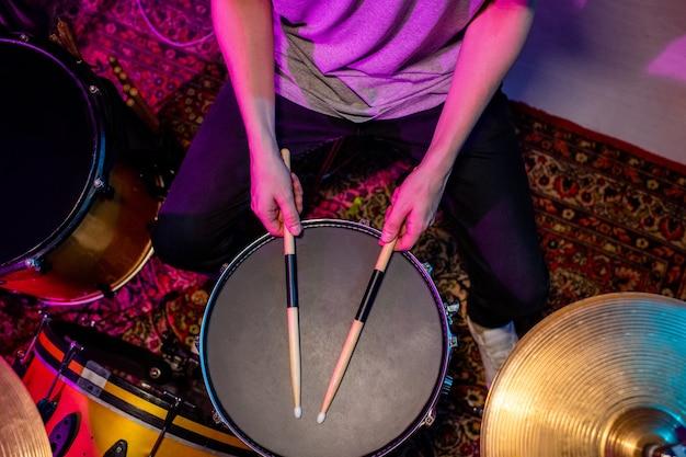 Mains de jeune batteur occasionnel touchant le haut du tambour en cuir noir avec des baguettes alors qu'il était assis par batterie pendant la répétition individuelle
