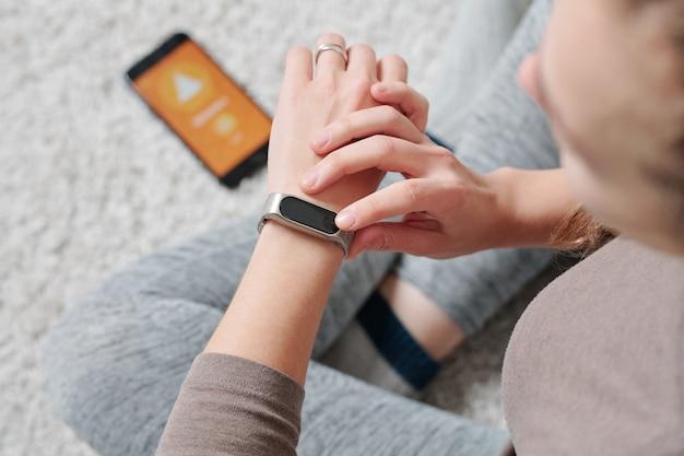 Mains De Jeune Femme Active Avec Smartwatch Assis Sur Le Sol Avec Ses Jambes Croisées Tout En Travaillant Photo Premium
