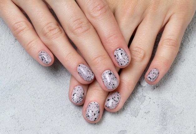 Mains de jeune femme adulte avec des ongles à la mode nude rose sur une table en béton gris
