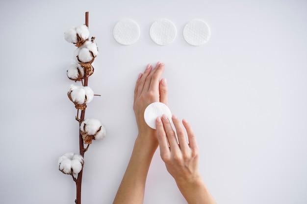 Mains d'une jeune femme avec une branche de coton, des tampons de coton sur fond blanc. manucure féminine. fleur de coton. concept de spa.