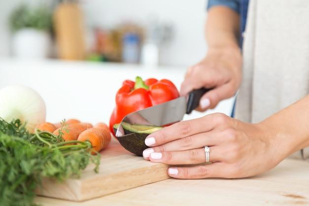 Mains de jeune femme coupe légumes frais dans la cuisine.