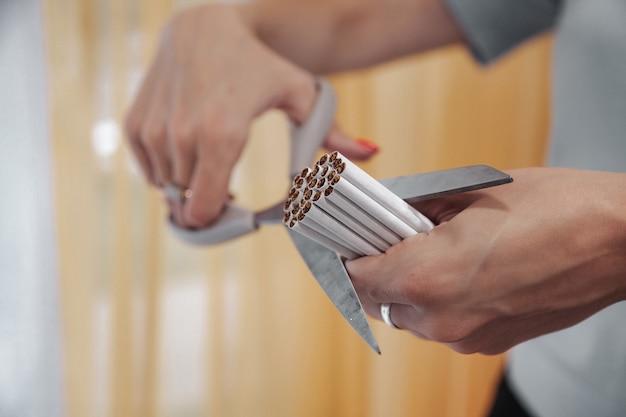 Les mains de la jeune femme coupent les cigarettes avec des ciseaux. quittez smok, combattez les addicts à la nicotine. gros plan de ciseaux coupant beaucoup de cigarettes. concept d'anti-tabac et de mode de vie sain. espace de copie